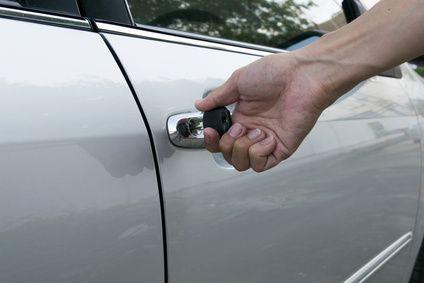 Hand öffnet Autotür